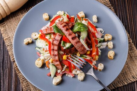Salad with grilled sausage paprica cucumber and croutons. Standard-Bild - 124900764