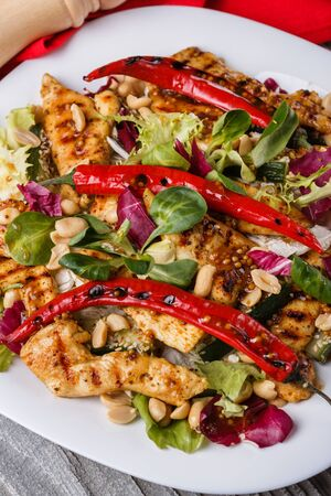 Mexican salad with hot pepper chiken fillet lettuce and nut on plate Standard-Bild - 124900769