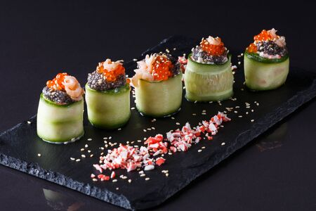 rolls covered in cucumber with caviar and prawn. Reklamní fotografie - 124900774