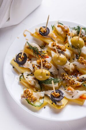 Salted herring on skewers with cheese and olives Banco de Imagens