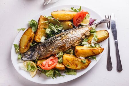 Baked stuffed fish with potatoes on the plate. Standard-Bild - 124900789