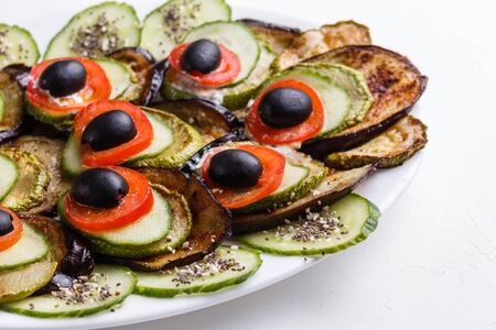 Baked eggplant and zucchini with fresh tomatoes,onions and olives. Standard-Bild - 124900788