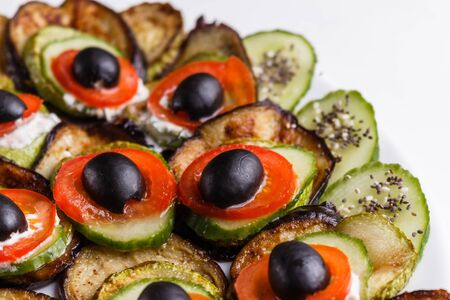 Baked eggplant and zucchini with fresh tomatoes,onions and olives. Standard-Bild - 124900790