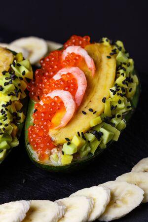 Avocado with banana caviar and shrimp. Standard-Bild - 124900794