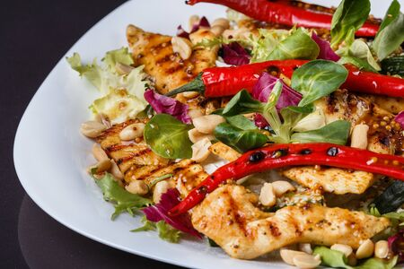 Mexican salad with hot pepper chiken fillet lettuce and nut on plate