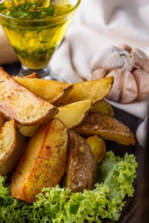 Potato wedges baked in their skins with lettuce on wooden background. A dish on a stoyn plate with a sauce in a glass pial. Stock Photo