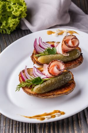 Twice baked potato with pickled cucumber, dill, salo and onion on wooden table.