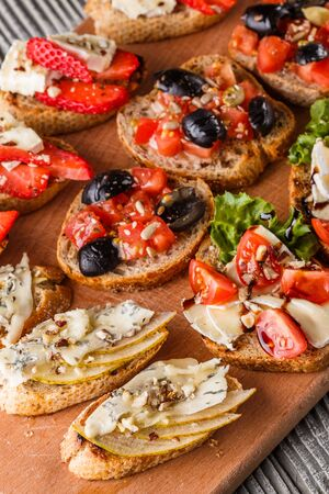 Assorted bruschetta with tomato, olives, camembert, blue cheese, lettuce, pear, honey on wooden board. Set of tasty appetizer sandwiches.