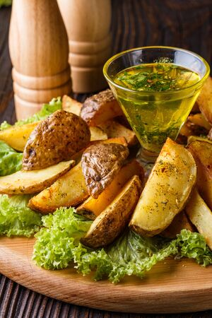 Potato wedges baked in their skins with lettuce on wooden background. A dish on a wooden plate with a sauce in a glass pial