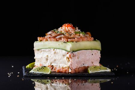 Piece of traditional savory swedish sandwich cake Smorgastorta with a caviar, mayonnaise, cucumber, square format
