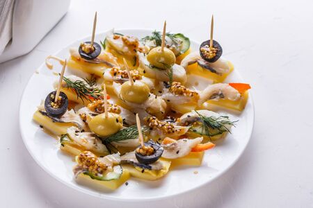 Salted herring on skewers with cheese and olives