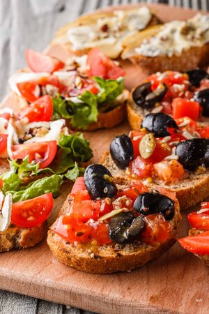 Assorted bruschetta with tomato, olives, camembert, blue cheese, lettuce, pear, honey on wooden board. Set of tasty appetizer sandwiches. 免版税图像