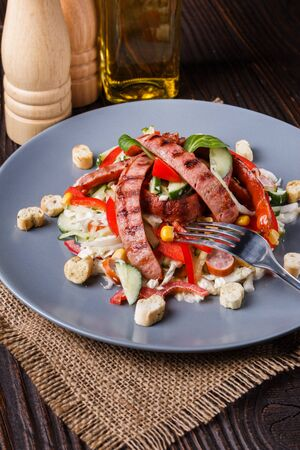 Salad with grilled sausage paprica cucumber and croutons. Stok Fotoğraf