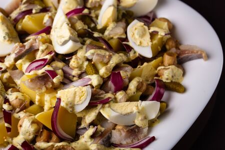 Salad with eggs onion potatoes and sause.