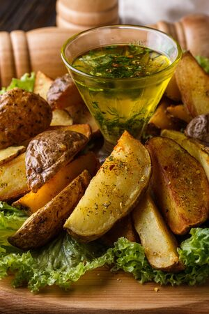 Potato wedges baked in their skins with lettuce on wooden background. A dish on a wooden plate with a sauce in a glass pial Imagens