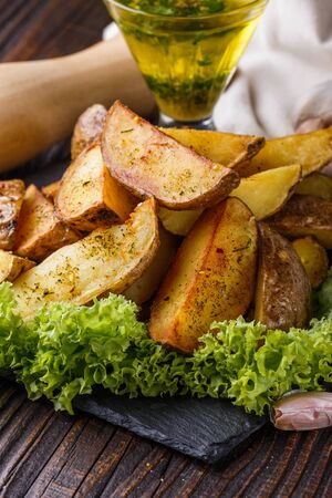 Potato wedges baked in their skins with lettuce on wooden background. A dish on a stoyn plate with a sauce in a glass pial. Stok Fotoğraf