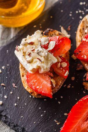 Bruschetta with strawberries, blue cheese, walnut and honey on stoyn plate.