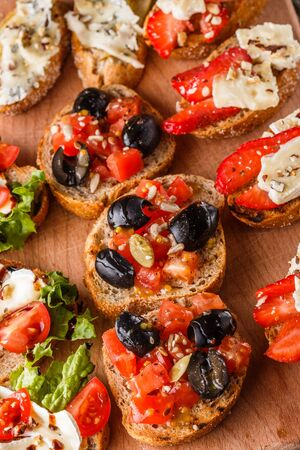 Assorted bruschetta with tomato, olives, camembert, blue cheese, lettuce, pear, honey on wooden board. Set of tasty appetizer sandwiches. Stok Fotoğraf
