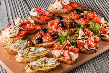Assorted bruschetta with tomato, olives, camembert, blue cheese, lettuce, pear, honey on wooden board. Set of tasty appetizer sandwiches. Imagens