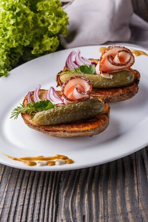 Twice baked potato with pickled cucumber, dill, salo and onion on wooden table. Imagens