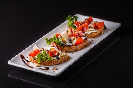 Bruschetta with tomatoes lettuce camambert balsamic vinegar.