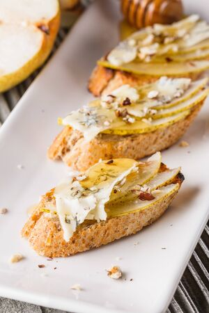 Appetizer bruschetta with pear, honey, walnut and blue cheese on white plate.