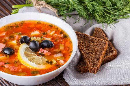 Traditional Russian meat and salt soup Solyanka in bowl on rustic wooden table. Imagens