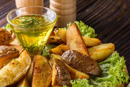 Potato wedges baked in their skins with lettuce on wooden background. A dish on a wooden plate with a sauce in a glass pial Stok Fotoğraf