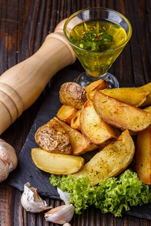 Potato wedges baked in their skins with lettuce on wooden background. A dish on a stoyn plate with a sauce in a glass pial. Imagens