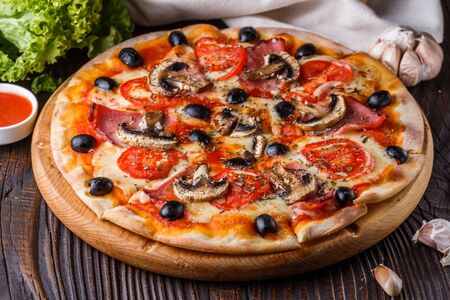Pizza with tomato, olives, champignons, ham and cheese on round wooden plate.