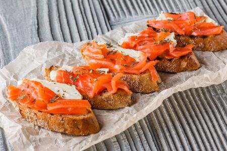 Bruschetta with smoked salmon and camembert on crumpled baking paper.