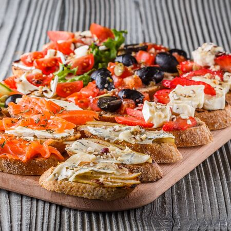 Assorted bruschetta with tomato, olives camembert blue cheese lettuce pear honey mustard balsamic vinegar cucumber on wooden board