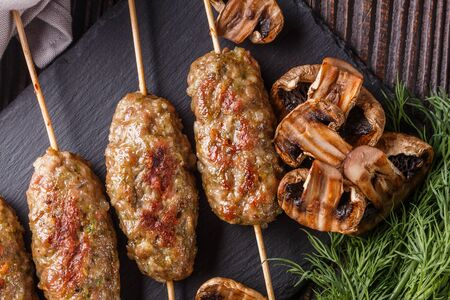 Shish kebab on the skewers with grilled mushrooms on rustic table. Фото со стока - 129814374