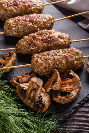 Shish kebab on the skewers with grilled mushrooms on rustic table.