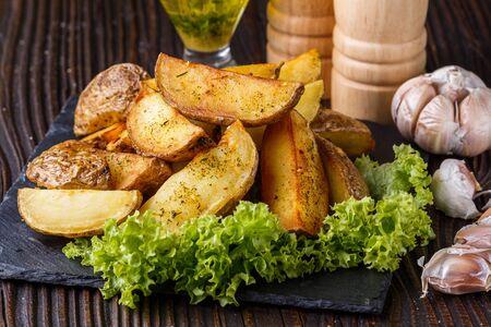 Kartoffelspalten in ihren Häuten mit Salat auf Holzhintergrund gebacken. Ein Gericht auf einem steinigen Teller mit einer Soße in einem Glaspial. Standard-Bild