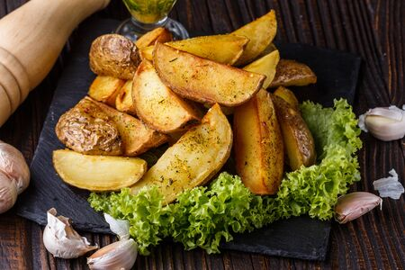 Potato wedges baked in their skins with lettuce on wooden background. A dish on a stoyn plate with a sauce in a glass pial. Zdjęcie Seryjne
