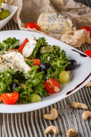 Salad provence. Mix lettuce tomato grape olive on wooden table.