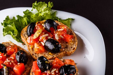 Italian bruschetta with tomato, black olives, lettuce and mustard. Zdjęcie Seryjne