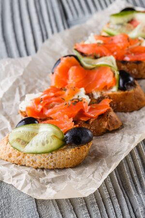 Bruschetta with smoked salmon, fresh cucumber, black olives and camembert on crumpled baking paper.