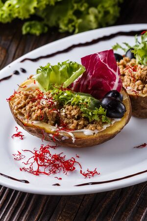 Twice baked potato stuffed with tune on white plate.