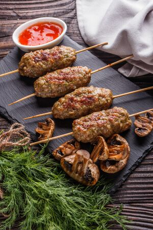 Shish kebab on the skewers with sauce, grilled mushrooms on rustic table.
