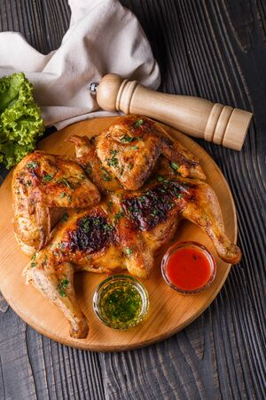 Roasted chiken on wooden board with sauce.