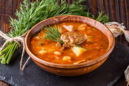 Chanahi a traditional Georgian meat stew in a bowl on stoyn board. Фото со стока