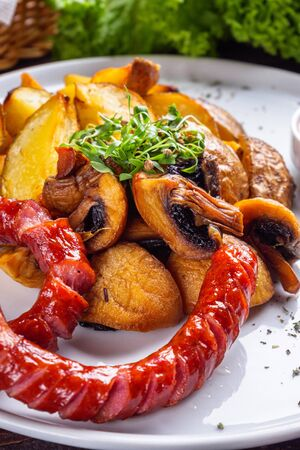 baked potatoes with sausages on a wooden rustic background.