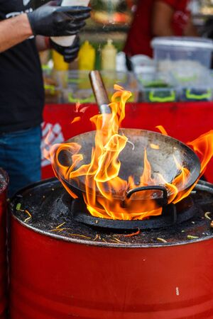 chef cooks Chinese noodle wok at street food festival.
