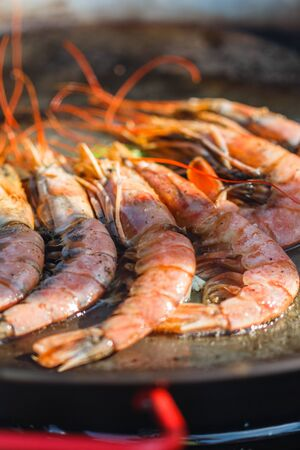 chef cooks shrimp at street food festival. 版權商用圖片