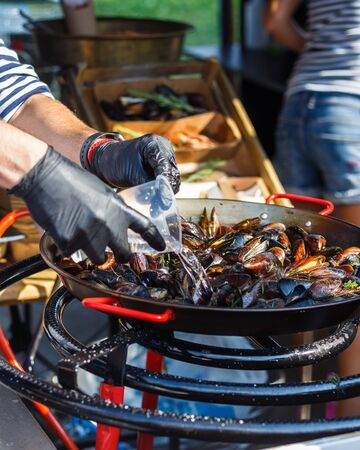 chef cooks mussels at the street food festival. 版權商用圖片