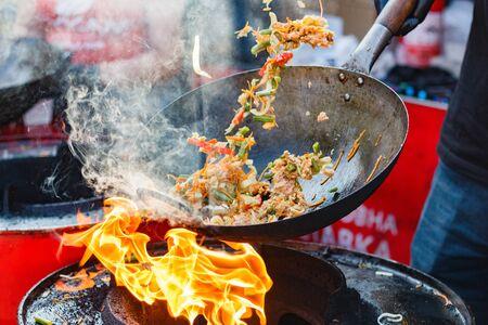 chef cucina wok di noodle cinesi al festival del cibo di strada.