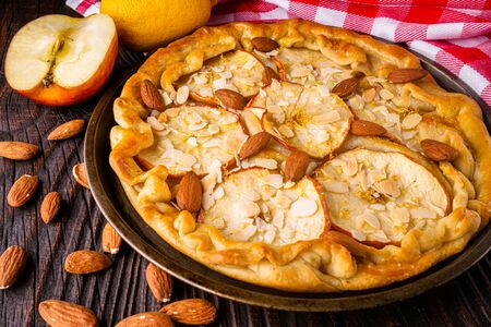 crispy apple galette with almonds on rustic wooden background.