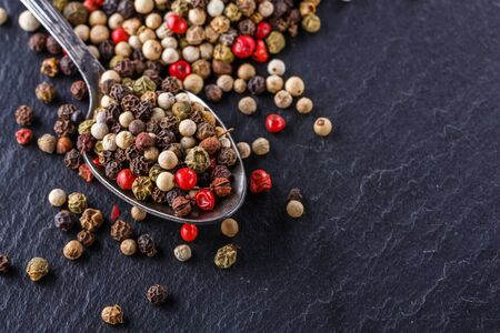 mix of peppercorns on a dark stone background.